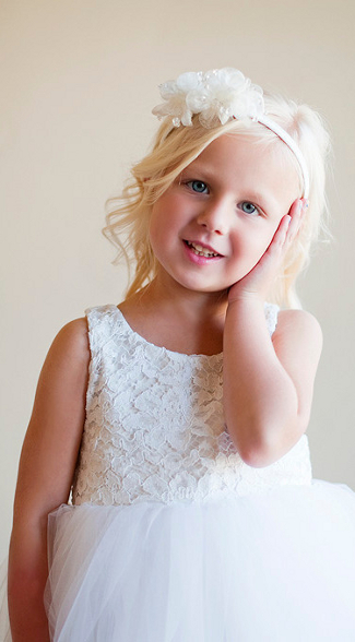 A picture of a beautiful flower girl dress with a lovely hairband wedding accessory on the cutest bridesmaid for a Gilly Gray Bridal wedding