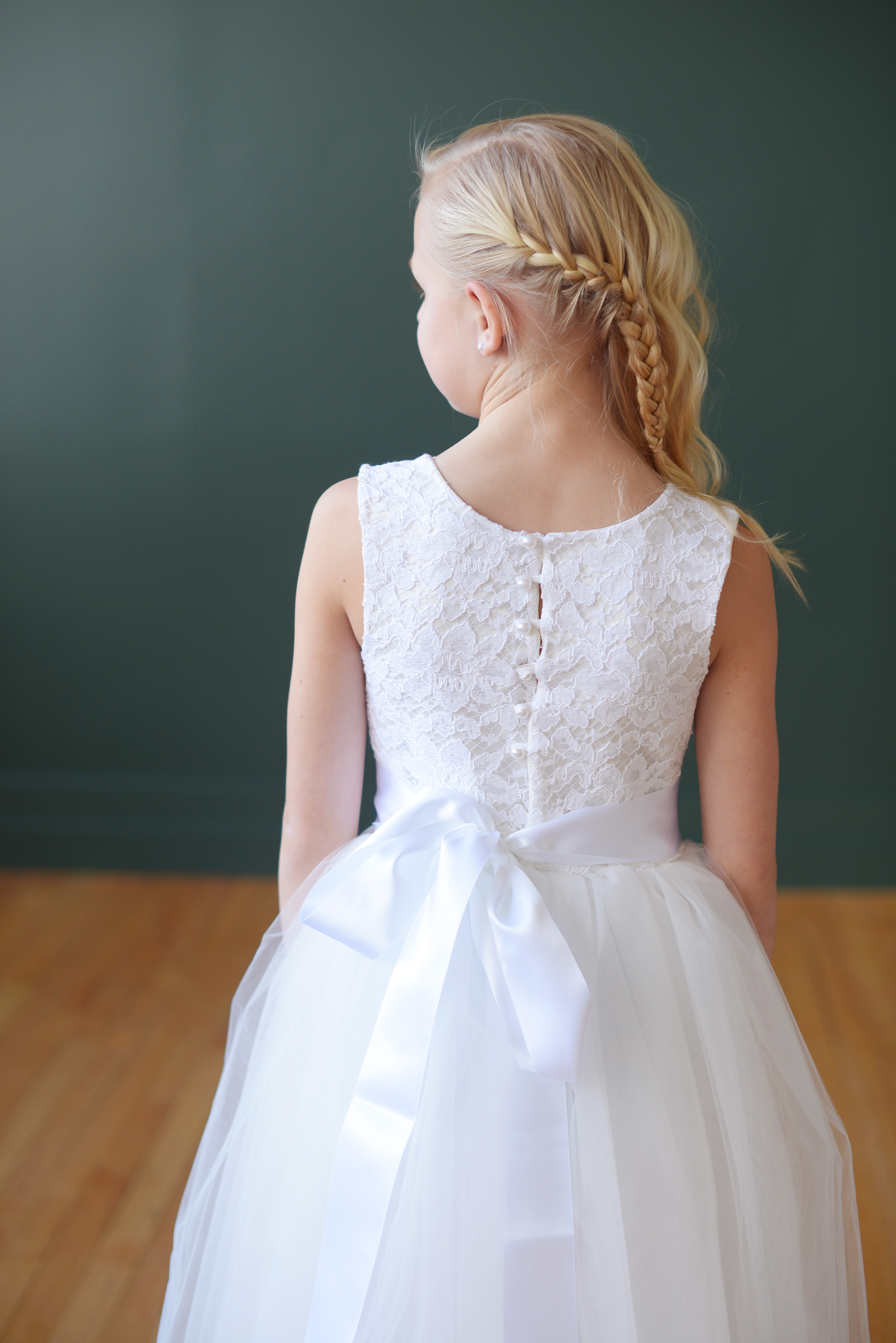 326ff1209 A white lace junior bridesmaid dress and flower girl dress with buttons at  he back and full tulle skirt.