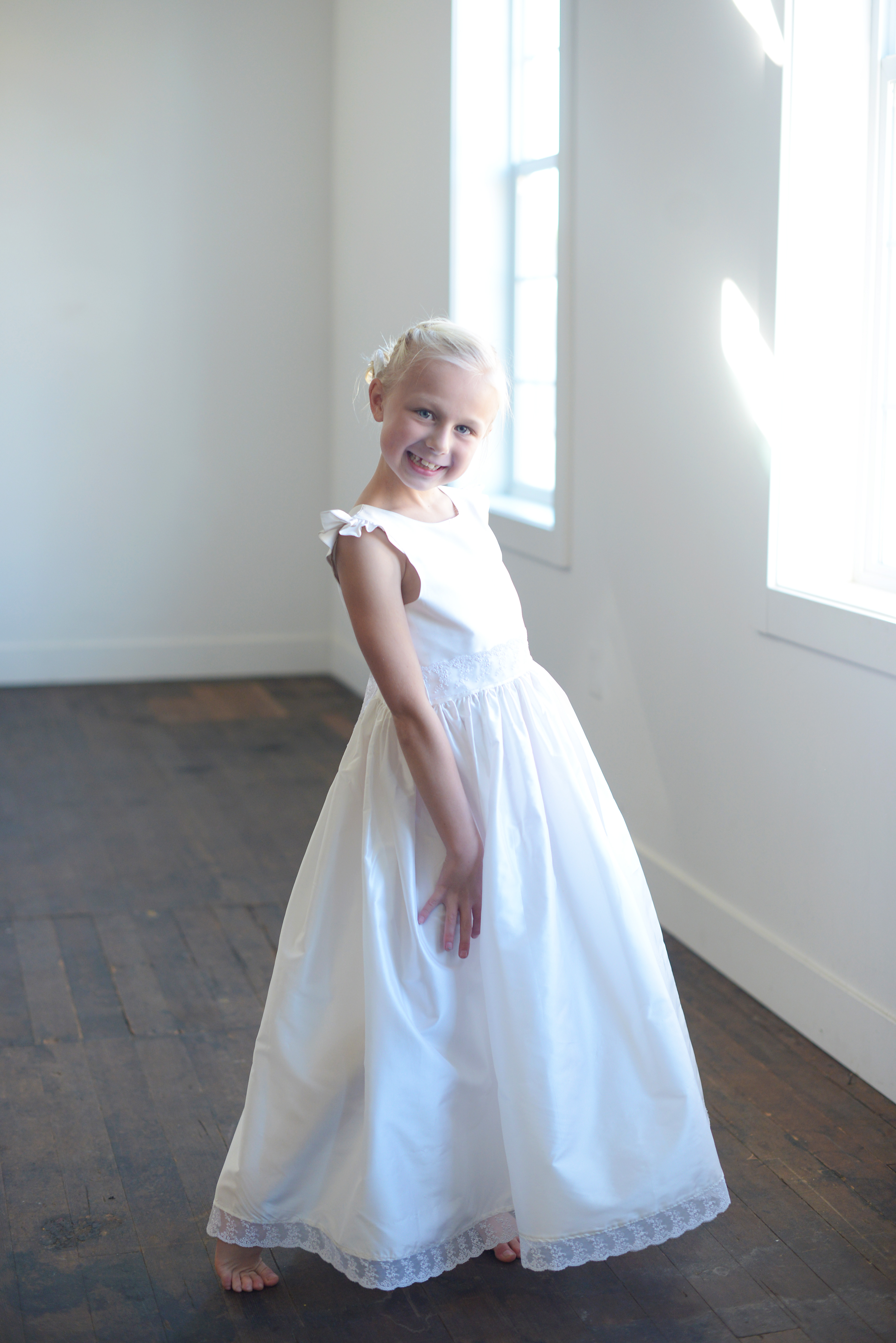 8e40ec2b449 A pure white First Communion dress with a lace sash and lace trim. The dress  has capped sleeves and is handmade to measure in pure wild silk.