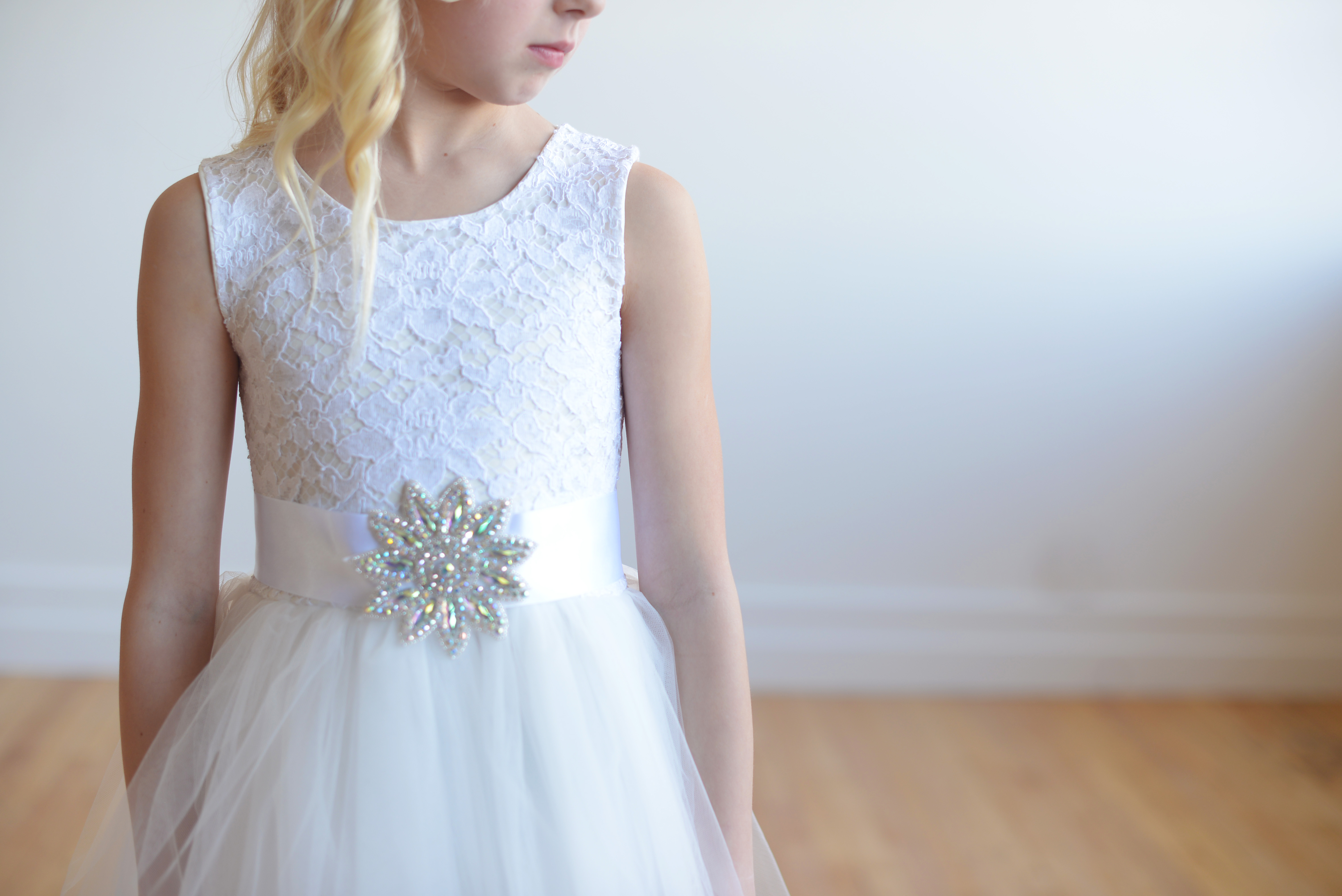 A White Lace Flower Dress With Full Tulle Skirt And Diamante Embellishment On The Sahsh