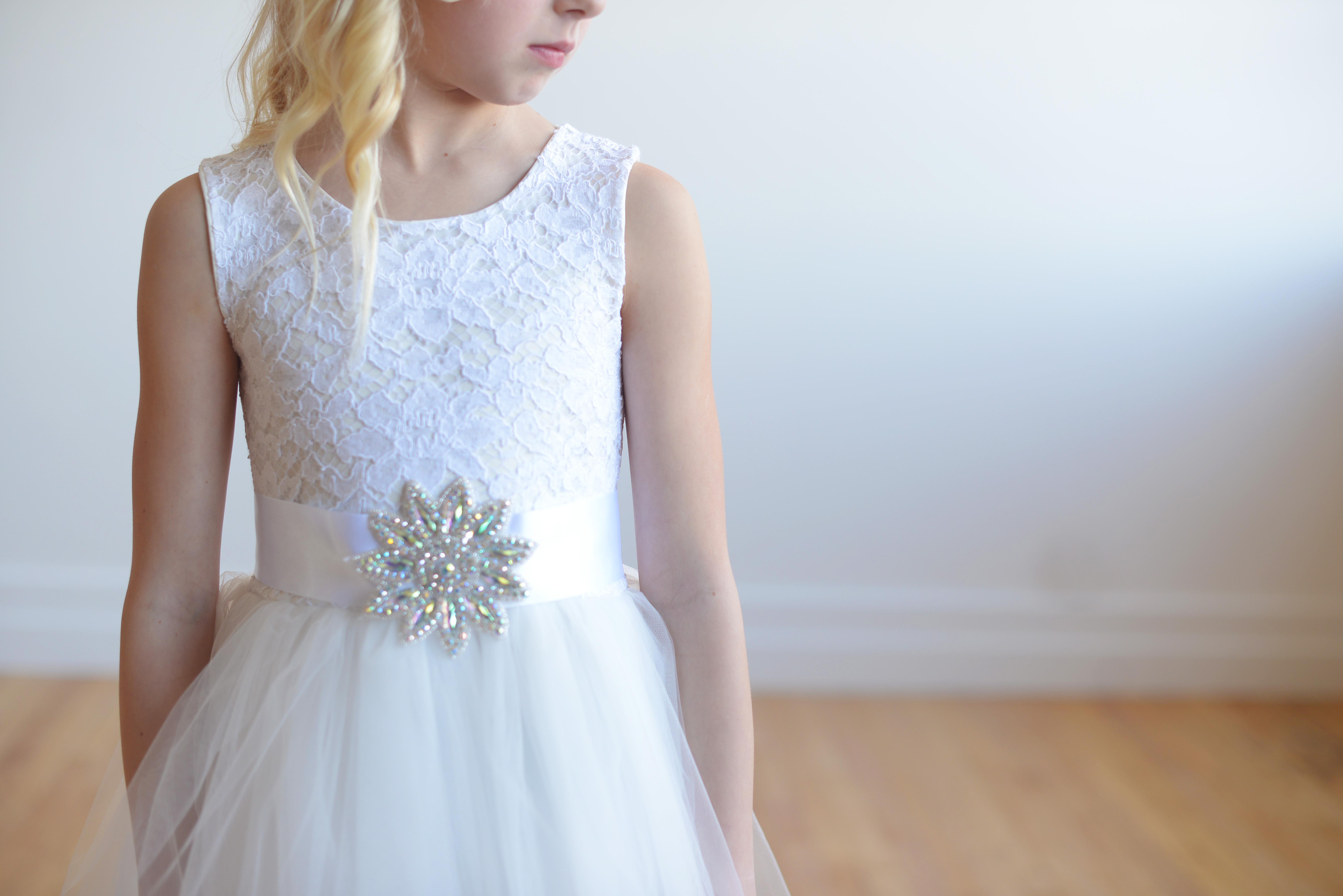 e903ed7e726 A white lace flower girl dress with full tulle skirt and diamante  embellishment on the sahsh.