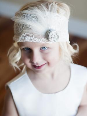 A flowergirl headband with rose and feather detail