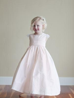 A photo of a made to measure pink silk flower girl dress with lace capped sleeve