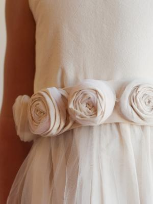 A photo of a cotton and tulle flower girl dress with a rosette belt in ivory