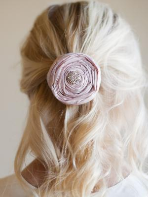 A photo of a rose hairclip in pink silk with diamante detail