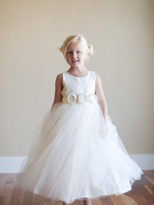 A photo of an ivory cotton flower girl dress with 3 rosettes on the sash