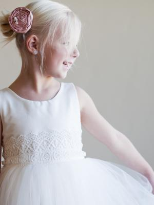 A cotton flower girl dress with a tulle skirt and lace belt and dusty pink