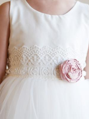 a white cotton or silk flower girl dress with lace belt and blush pink flower