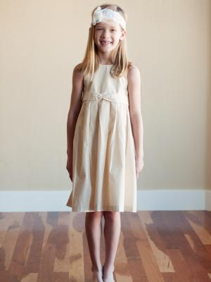 A photo of a cotton flower girl dress inivory or white witha rosette detail