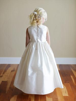 A white silk flower girl dress with Peter Pan collat