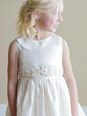 A girl wearing a silk flower girl dress with peter pan collar
