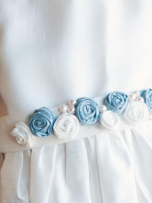 A photo of a satin flower girl dress with forget me not flowers and pearls