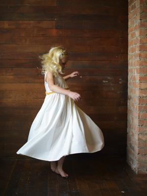 A little girl spinning in a cotton flower girl dress