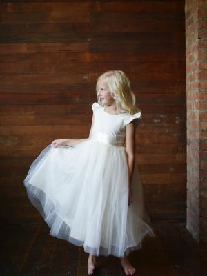 a silk flower girl dress with capped sleeves and a full tulle skirt