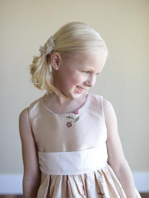A close up of a blush silk hand made flower girl dress