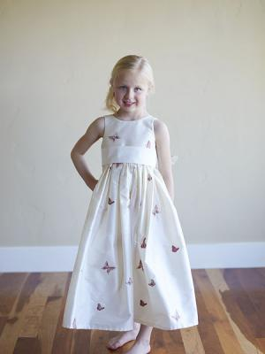 A white silk girls flower girl dress with embriodered butterfly detail