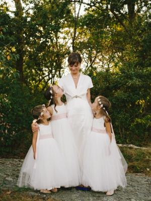 an ivory flower girl dress with tulle skirt  and dusky pink sash for wedding