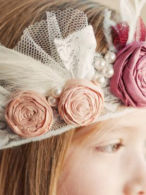 A photo of a 1920s style flower girl headband with silk rosettes and feathers