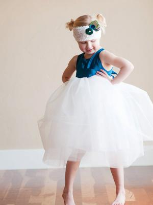 A photo of a flower girl dress with a peacock blue bodice and tulle skirt - this