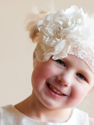 A photo of a satin and lace headband witha large peony flower for flower girls