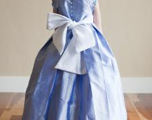A photo of a silk flower girl dress with button back, wide satin sash and sleeve