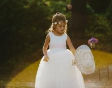 a photo of a traditional flower girl dress with tulle skirt and pink sash