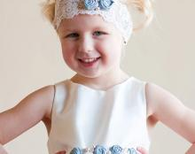 A photo of a satin flower girl dress with forget me not flowers on the sash