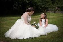 White flower girl dress with lace and tulle. The dress has a custom motif on the sash in diamante.
