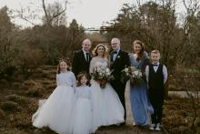 A wedding party with the bride in an ivory tulle wedding dress and flower girls wearing ivory and pink tulle dresses.
