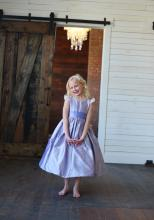 A flower girl wearing a flower girl dress in purple silk. The dress has lace sleeves and a wide silk sash which ties in a big bow.