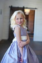 A junior bridesmaid and a baby and toddler each wearing a pretty purple silk junior bridesmaid dress with white lace sleeves. The skirt of this dress is very full and  it has a wide satin sash which ties in a big bow at the back.
