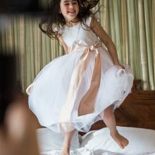An ivory or white cotton and silk flower girl dress with a pink bow