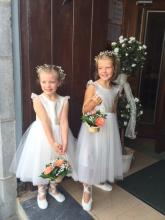 A toddler flower girl and a baby at a church wedding. The baby is wearing a sherbet lemon dress with pink flowers and the toddler flower girl is wearing an ivory flower girl dress with white accents.