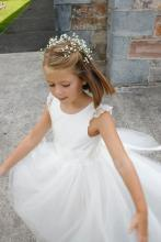 A toddler flower girl at a church wedding in the countryside. The flower girl is wearing anivory silk flower girl dress with a tulle skirt. She is throwing pink, peach and sherbet lemon flowers at the guests.