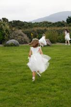 A toddler flower girl running throughthe grass wearing an ivory silk flower girl dress with a big bow and lace flutter sleeves. The flower girl is chasnig a junior bridesmaid who is wearing a white junior bridesmaid dress with sherbet lemon and pink flowers.