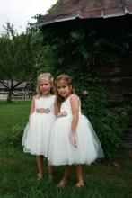 A bride in the USA wearing and her three toddler flower girls. The flower girls are wearing bespoke ivory flower girl dresses with tulle skirts. The dresses have pink and sherbet lemon flowers on the sash.