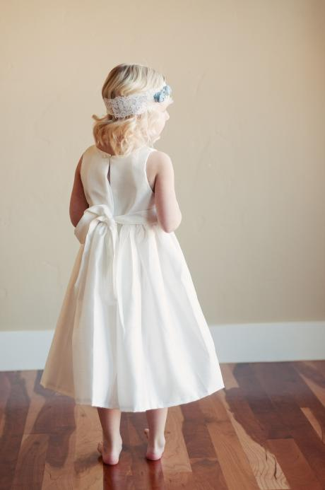 A toddler flower girl wearing a white flower girl dress with pretty blue silk flowers.