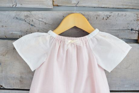 Detailed photo of the clementine dress with small ribbon bow, sleeves and lace hem.
