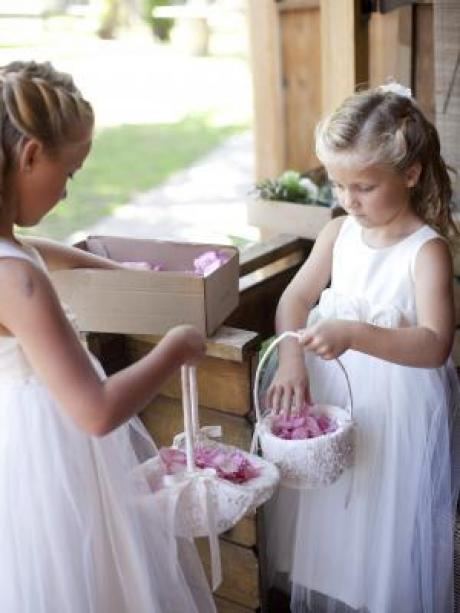 Two girls with flower girl baskets and pink petals wearing cotton flower girl dresses with tulle skirts.