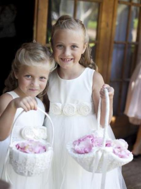 Two girls at a wedding wearing an ivory cotton dress which has flowers on the belt and a tulle skirt.