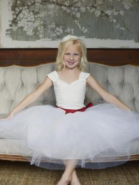 A flower girl at a wedding sitting on a chair wearing a white tutu flower girl skirt with a red sash with big bow.