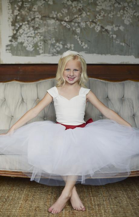 A young flower girl sitting on a couch wearing a red and white tulle tutu with a a big bow at the back. The flower girl is also wearing a satin covered Alice band in her hair with diamante and a feather.