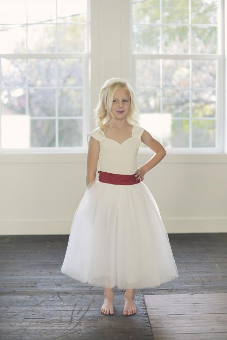 A young flower girl at a wedding wearing a white flower girl tulle skirt with a red waist band and big bow.