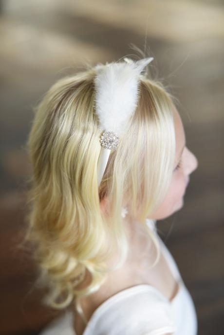 A young flower girl wearing a handmade satin covered alice band with diamante and feathers.