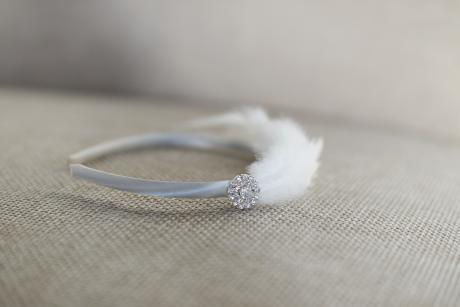 A close up of a satin covered ivory and white headband for flower girls with diamante and a feather.