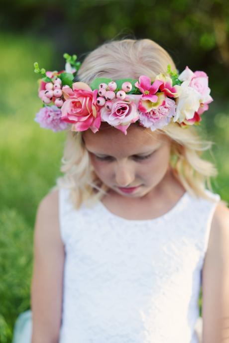 A close up of a young flower girl at a wedding wearing a flower girl crown for a wedding.