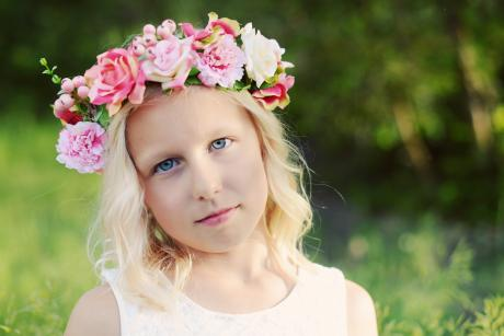 A flower girl at at wedding a wearing a flower wreath with pink, ivory and green flowers.