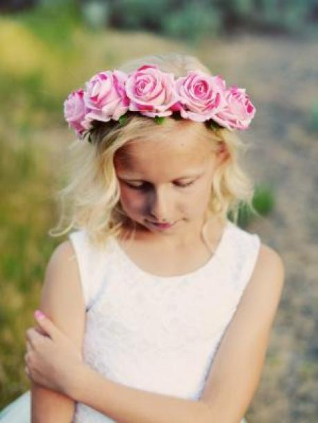 A young girl in the countryside wearing a pink rose headband and a white flower girl dress