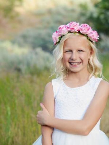 A 7 year old girl smiling and wearing a pink rose headband and a white lace flower girl dress