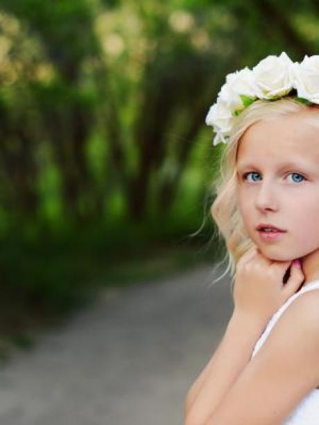 A flower girl wearing an ivory rose headband